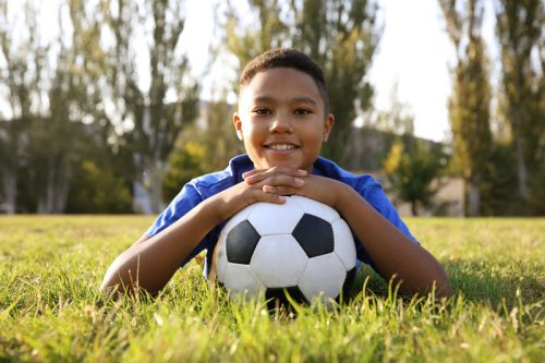 youth soccer player laying in grass