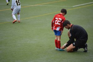 Child Having His Shoe Laces Tied By Trainer In Soccer League For Kids