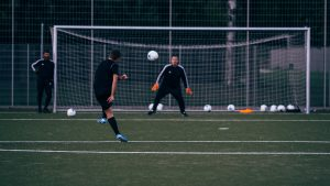 Soccer Player Taking A Shot Towards The Goalkeeper During Soccer Lessons For Beginners